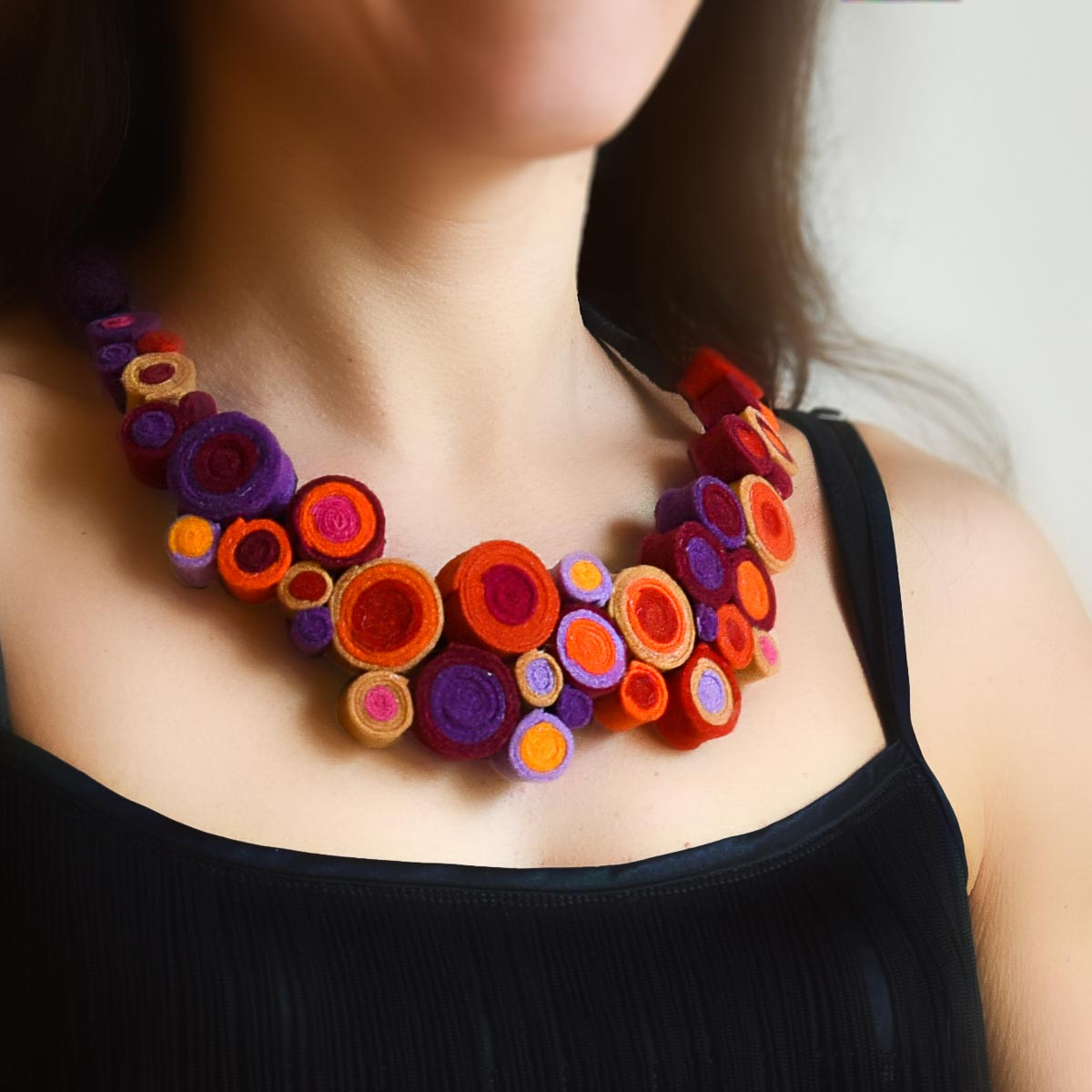 Blooming jewelry consists of two large statement collar necklaces inspired by the colorful variety of flower gardens. The jewelry is made with felt beads and looks like a blooming garden.